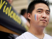 "A demonstrator with his face painted with a French flag stands next to a banner with the word ""violence"" at a rally of the Chinese community to raise awareness about recent racists attacks in Paris"