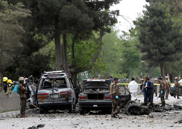 Afghan security forces inspect the site of a suicide attack in Kabul, Afghanistan