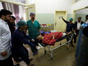Men carry an injured man inside a hospital after a suicide attack in Kabul